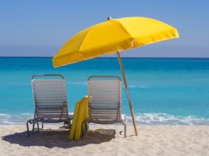 """Yellow Beach umbrella and deck chairs on the beach on a clear day on South beach, Miami"""