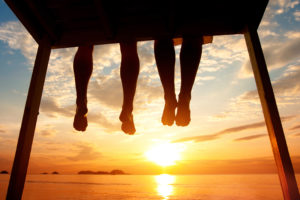 happiness concept, silhouette of feet of couple sitting on the pier at sunset beach