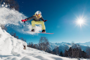 Young woman is jumping with snowboard on mountain